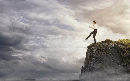 over the edge: Risk, young businesswoman walking over the edge of the cliff