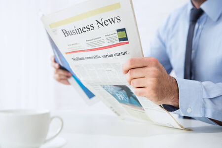 Close up of young businessman reading business news photo