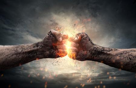 Combattre, gros plan de deux poings qui se frappent dans un ciel dramatique