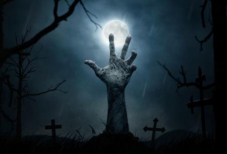 cementerios: Concepto de Halloween, mano del zombi que emergen de la tierra