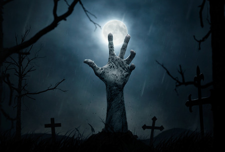 on coming: Halloween concept, zombie hand rising out from the soil Stock Photo