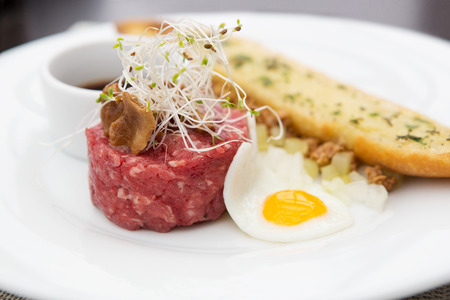 Close up of tartare beef with fried egg, chanterelle and garlic bread