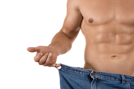 weight loss man: Loosing weight, close up of muscular built man wearing too large jeans isolated on white background
