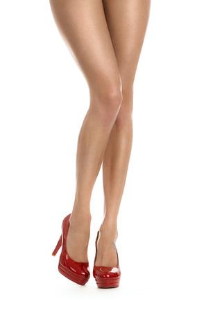 Close-up van perfecte vrouwelijke poten met rode hakken op een witte achtergrond