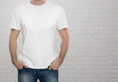 コピー スペースと白いレンガ壁を越えて空白の t シャツを着た男