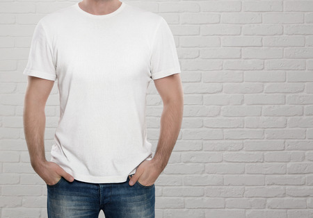 Man wearing blank t-shirt over white brick wall with copy space photo