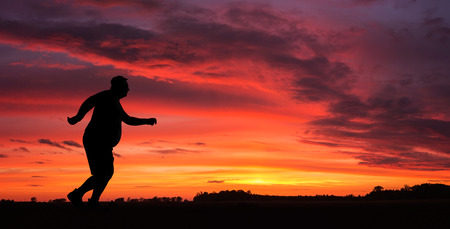 Silhouette of funny overweight man jogging at the sunset Archivio Fotografico