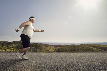 fat: Funny overweight man jogging on the road Stock Photo