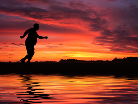 Silhouette of overweight man running at the sunset photo