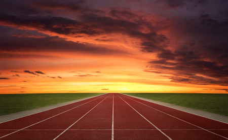 Lege eindeloze atletiekbaan bij de zonsondergang Stockfoto