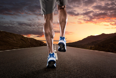 coureur: Gros plan de l'athl�te courir sur la route d�serte au coucher du soleil