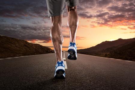 Nahaufnahme von Athleten auf der leeren Straße, die in den Sonnenuntergang