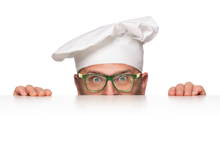 Funny overweight chef peeking from behind the banner isolated on white background photo