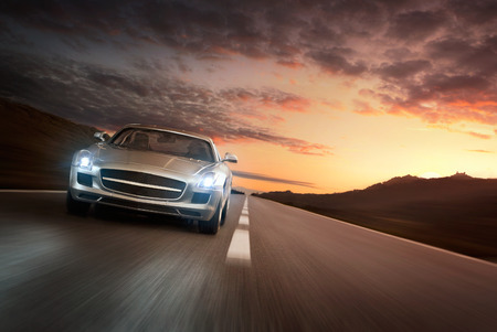 headlights: Luxury sports car speeding on a highway at the sunset