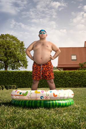 Cheap holidays at home, funny overweight man about to swim in the back yard pool
