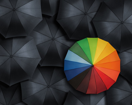 Standing out from the crowd, high angle view of colorful  umbrella over many black ones
