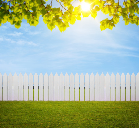 Close up of white wooden fence in the back yard with copy space photo