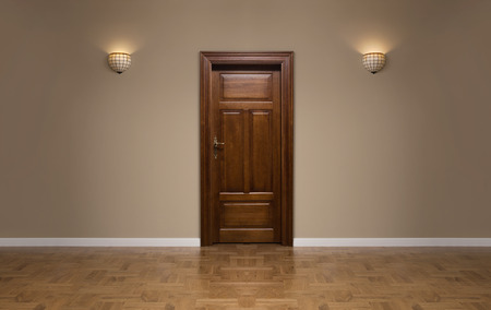 Close up of closed wooden door in the empty room with copy space photo