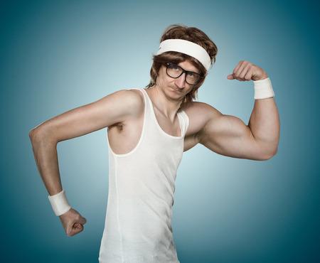 geek: Empollón retro divertido con un brazo enorme flexionando su músculo sobre fondo azul Foto de archivo