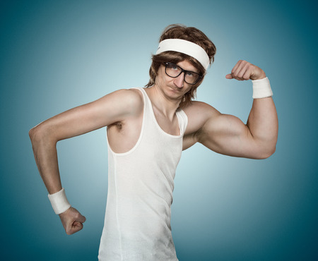 Grappig retro nerd met een enorme arm buigen zijn spieren over blauwe achtergrond