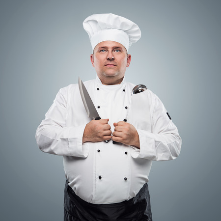 Funny overweight chef over blue background photo