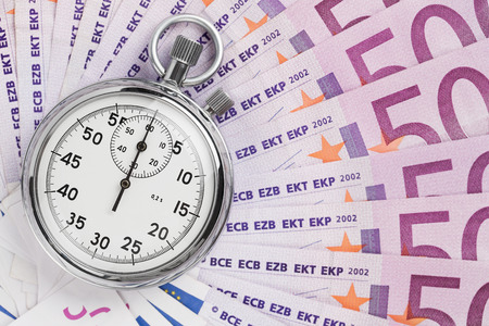 Time is money concept, analog stopwatch on the euro banknotes photo