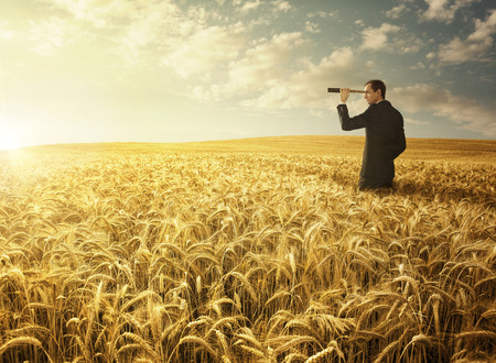 Young businessman in the wheat field searching for the new opportunites