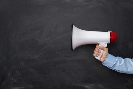 Close up of businessmans hand holding megaphone over dark background with copy space