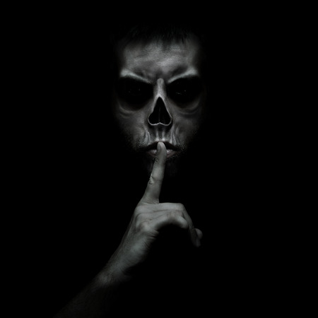 Evil man gesturing silence, quiet isolated on black background