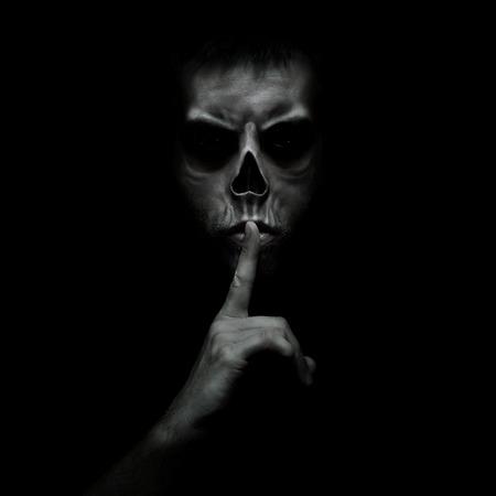 Hombre malvado gesticulando silencio, tranquilo aislado sobre fondo negro Foto de archivo