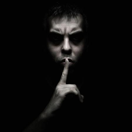 stil zijn: Kwade man gebaren stilte, rustige geïsoleerd op zwarte achtergrond Stockfoto