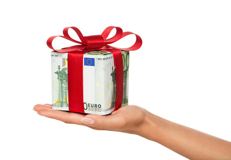 Close up of female hand holding gift made of euro banknotes isolated on white background