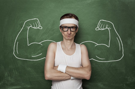 sport training: Funny sport nerd with fake muscle drawn on the chalkboard