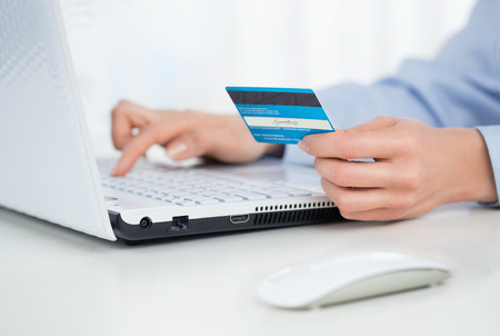 pay bill: Close up of female hands making online payment