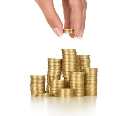 Close-up van vrouwelijke hand stapelen van gouden munten geïsoleerd op een witte achtergrond