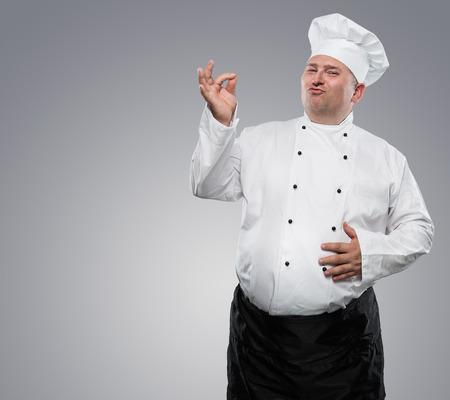 Grappige chef overgewicht blijkt ok geïsoleerd op een grijze achtergrond met een kopie ruimte
