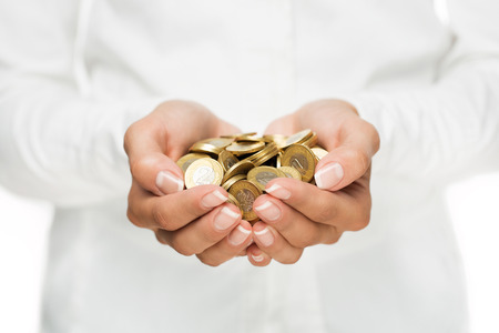 Savings, close up of cupped female hands holding golden coins Archivio Fotografico