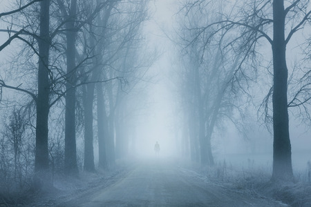 mystery of faith: Silhouette of a lonely man standing on the foggy road