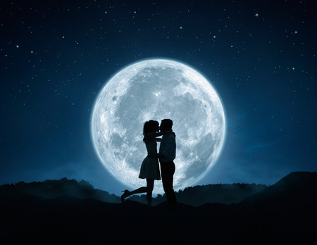Silhouette of loving couple kissing agains the full moon 스톡 콘텐츠