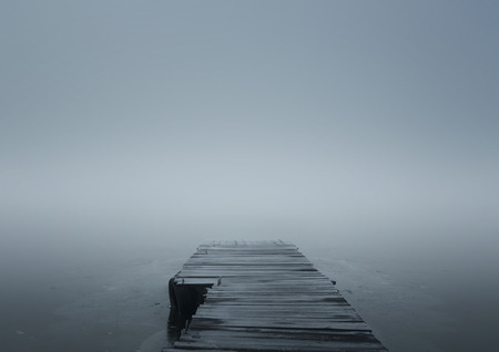 Close up of wooden jetty in the winter fog with copy space Standard-Bild