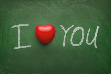 I love you text written on the chalkboard with red rubber heart photo