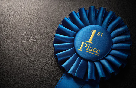 first place: First place award rosette over dark background with copy space Stock Photo