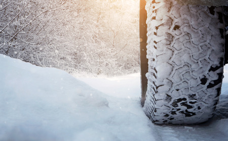 road conditions: Close up of car tire on the snowy road with copy space Stock Photo