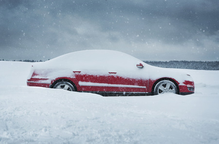Winter, close up of red car covered with the snow