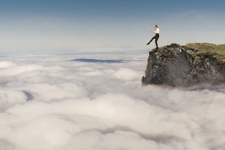 risk ahead: Risk concept, young businesswoman walking on the edge of the cliff above the clouds