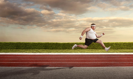 Funny overweight man speeding on the running track with copy space