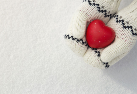 white gloves: Winter , close up of little girls hands holding red rubber heart with copy space