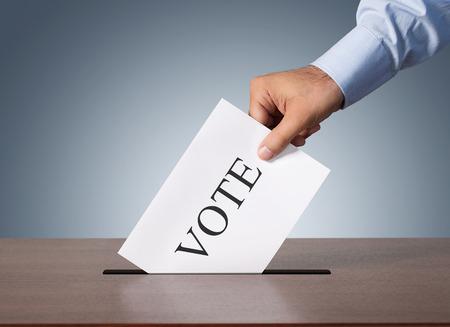 Cerca de la mano masculina poniendo voto en una caja de balot