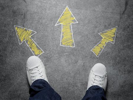 carretera: Decisiones, vista de �ngulo alto de tres flechas apuntando en distintas direcciones dibujadas en la calle