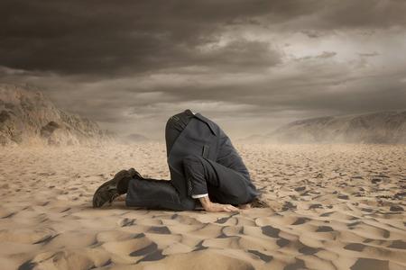 avestruz: Hombre de negocios joven que oculta la cabeza en la arena Foto de archivo